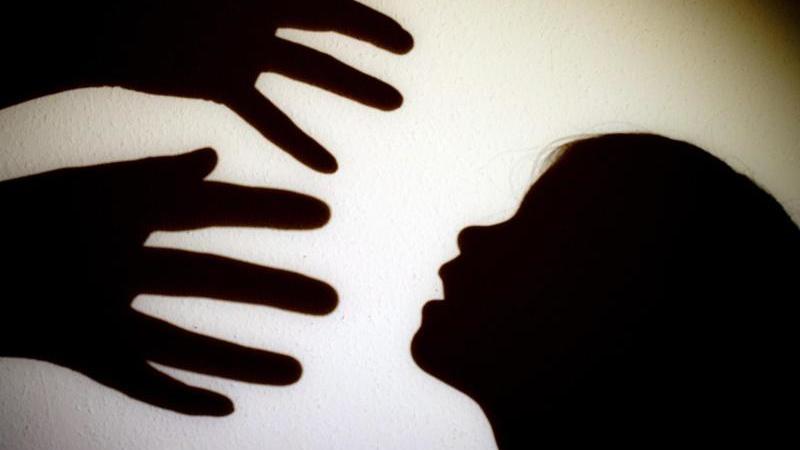 Eine Illustration zeigt einenSchatten von Händen einer erwachsenen Person und dem Kopf eines Kindes. Foto: Patrick Pleul/zb/dpa/Symbolbild