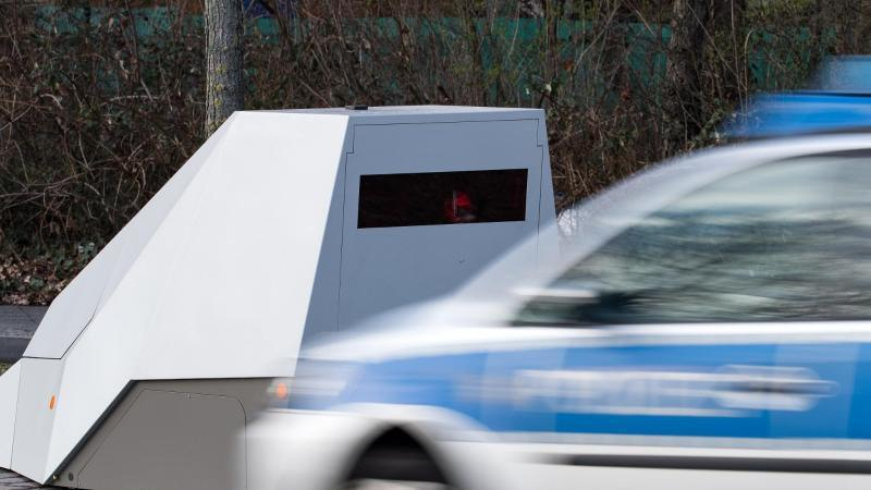 Ein Polizeiwagen fährt an einem mobilen Blitzwagen vorbei. Foto: Bernd von Jutrczenka/dpa/Symbolbild
