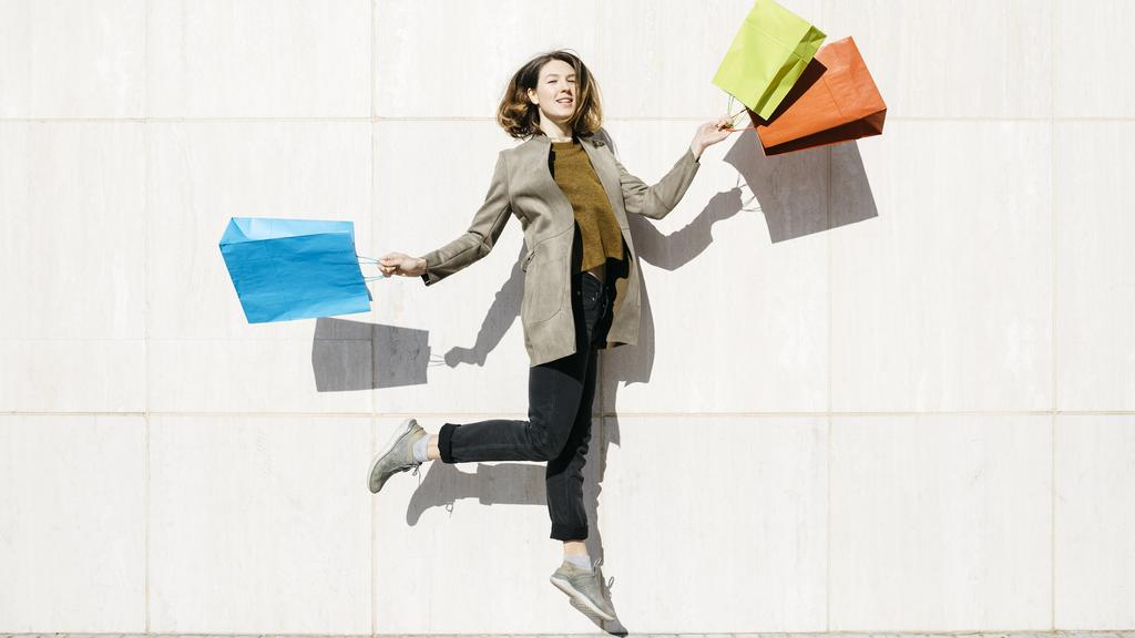 Cheerful woman with shopping bags jumping at a wall model released Symbolfoto PUBLICATIONxINxGERxSUIxAUTxHUNxONLY JRFF02783