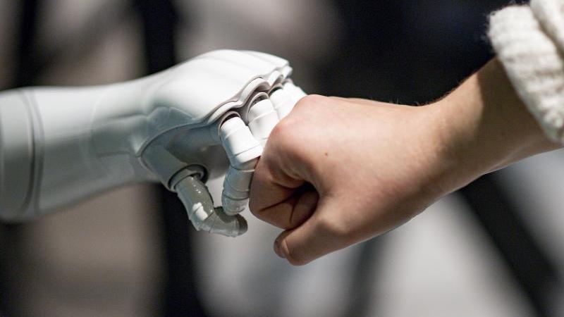 Ein Roboter interagiert mit einer Frau. Foto: Axel Heimken/dpa