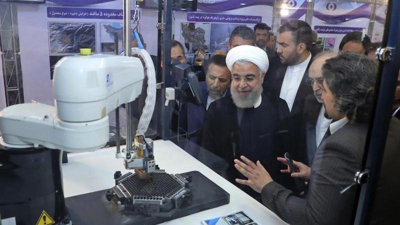 """Der iranische Präsident Hassan Ruhani (M.) lässt sich neue Entwicklungen in der Atomenergie im Rahmen des """"Nationalen Atomtags"""" erklären. Foto: Uncredited/Iranian Presidency Office/AP/dpa"""