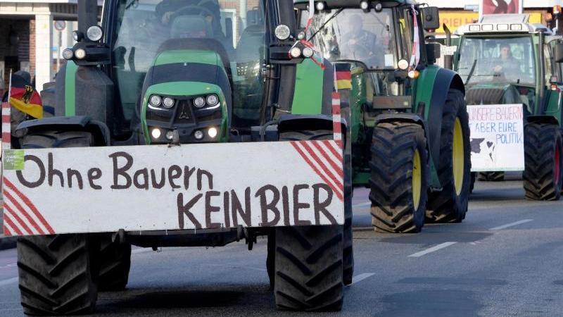 """Schlagendes Argument:Landwirte nach einer Sternfahrt in Kiel. An einem Trecker warnt ein Schild mit der Aufschrift """"Ohne Bauern KEIN BIER"""". Foto: Carsten Rehder/dpa"""