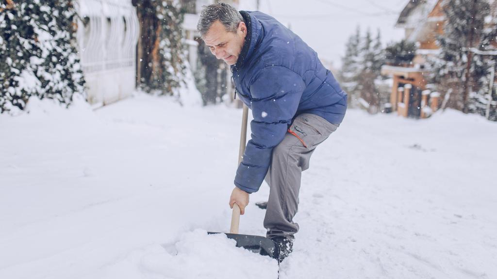 Alter Mann beim Schnee schippen
