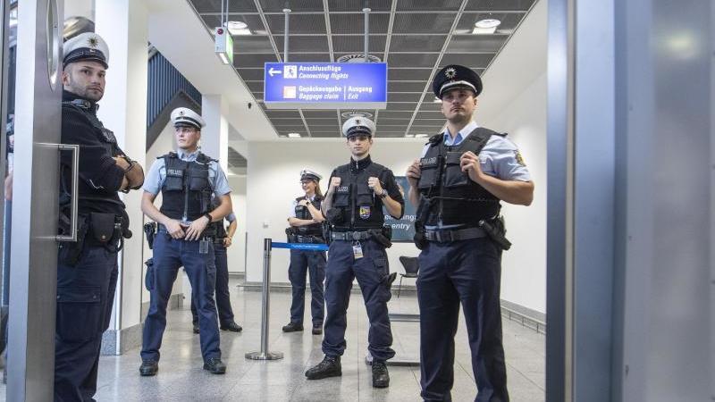 Beamte der Bundespolizei führen an einem Gate am Flughafen eine Einreisekontrolle durch. Foto: Boris Roessler/Archiv