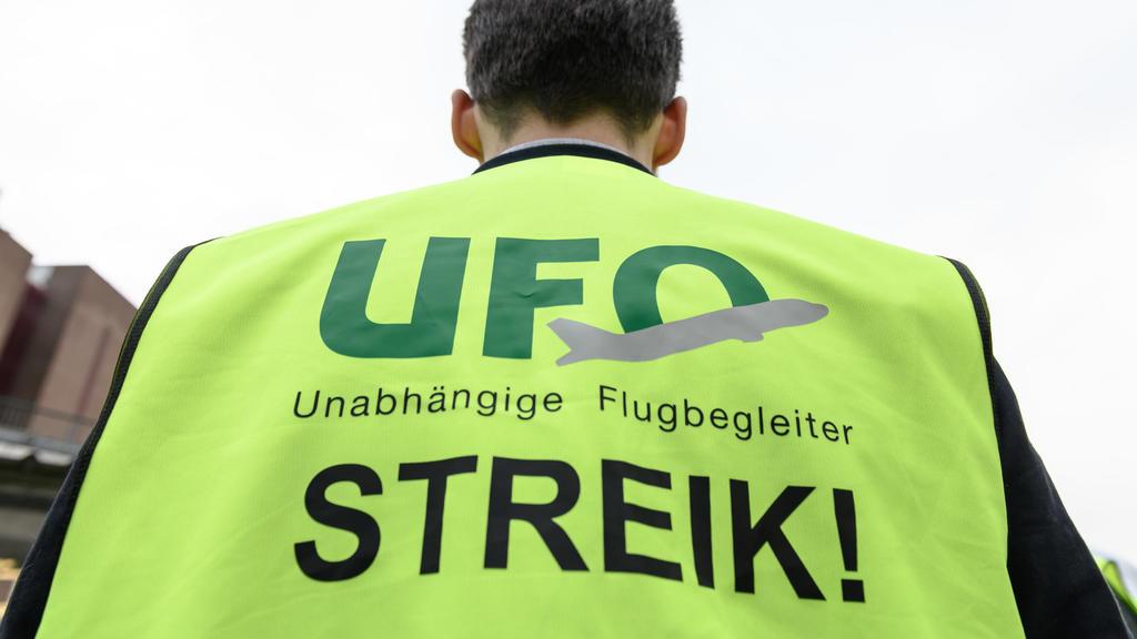 ARCHIV - 20.10.2019, Hessen, Frankfurt/Main: Ein Mann steht mit einer Warnweste mit der Aufschrift «Streik» an Tor 20 des Frankfurter Flughafens. Die Kabinengewerkschaft Ufo hat einen weiteren Streik der Flugbegleiter im Lufthansa-Konzern angekündigt