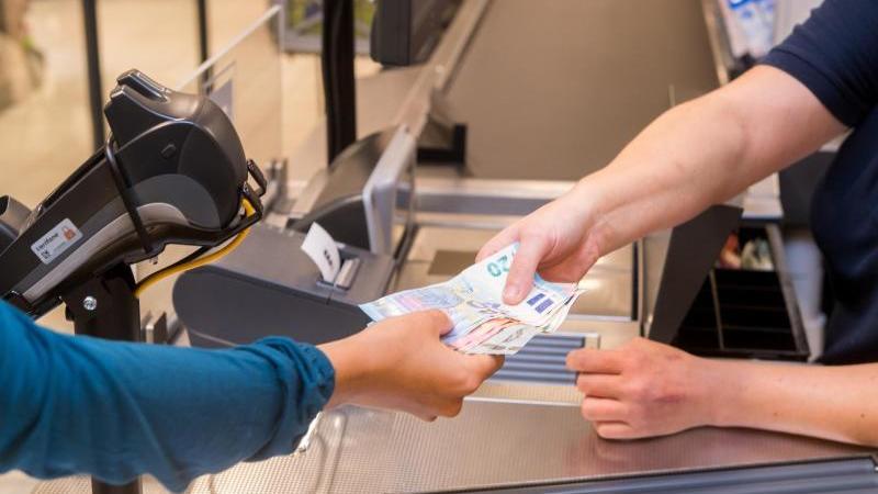 In einem Supermarkt bezahlt eine Kundin mit Bargeld. Kann sich auf den Banknoten auch das Coronavirus halten?