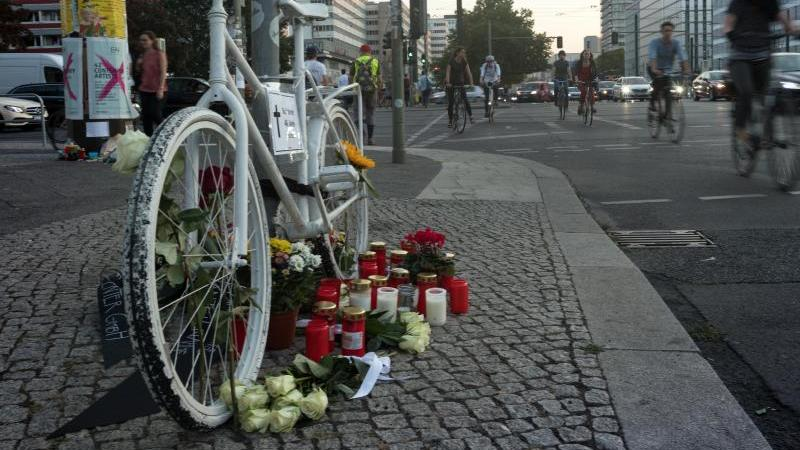 Blumen und Kerzen liegen vor einem weißen Geisterrad. Foto: Soeren Stache/dpa/Archivbild