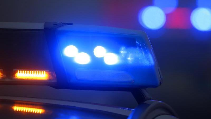 Ein Polizeiauto mit eingeschaltetem Blaulicht steht an einer Unfallstelle. Foto: Karl-Josef Hildenbrand/dpa/Archivbild