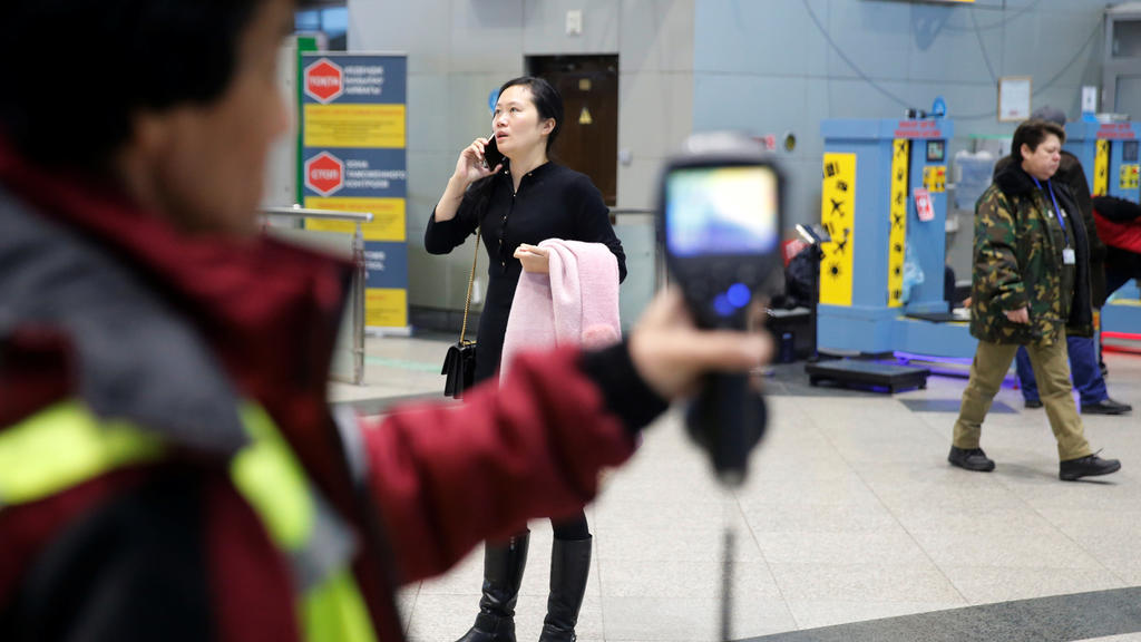 Kazakh sanitary-epidemiological service worker uses a thermal scanner to detect travellers from China who may have symptoms possibly connected with the previously unknown coronavirus, at Almaty International Airport, Kazakhstan January 21, 2020. REUT