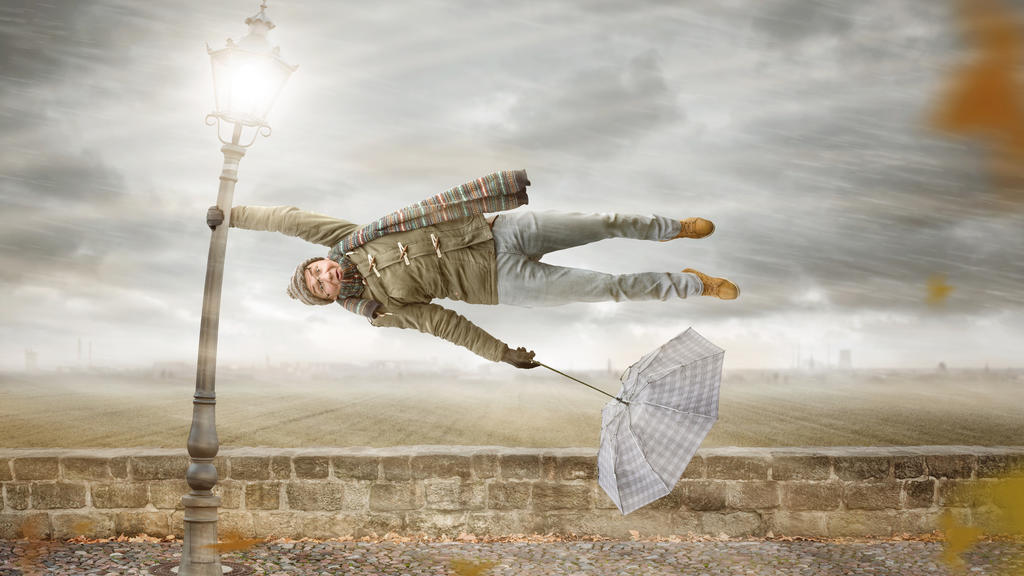 A funny man with an umbrella is holding on to a lamp post while a heavy storm ist blowing. The man is flying horizontally in mid air.