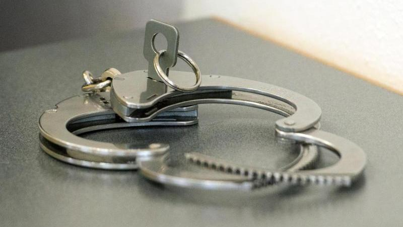 Handschellen liegen auf einem Tisch. Foto: Armin Weigel/dpa