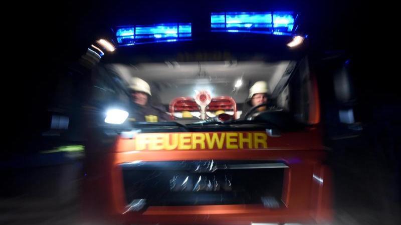 Männer der Feuerwehr sitzen in einem Löschfahrzeug. Foto: Carsten Rehder/dpa