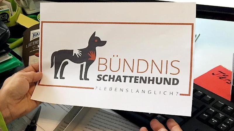 """Inge Wanken sitzt in ihrem Büro und zeigt das Logo """"Bündnis Schattenhund"""". Foto: Birgit Reichert/dpa/Archiv"""