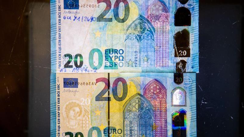 Fälschung und Original: Um einen echten Geldschein (unten) von einer nachgemachten Banknote (oben) unterscheiden zu können, sollten Bankkunden auf die Sicherheitsmerkmale achten. Foto: Julian Stratenschulte/dpa