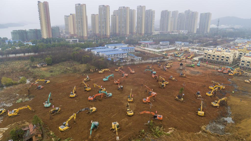 24.01.2020, China, Wuhan: Arbeiter mit schwerem Gerät errichten ein Lazarett. China baut in aller Schnelle ein Krankenhaus mit 1.000 Betten, das für Patienten bestimmt ist, die mit dem neuen Virus infiziert sind. Foto: CHINATOPIX/AP/dpa +++ dpa-Bildf