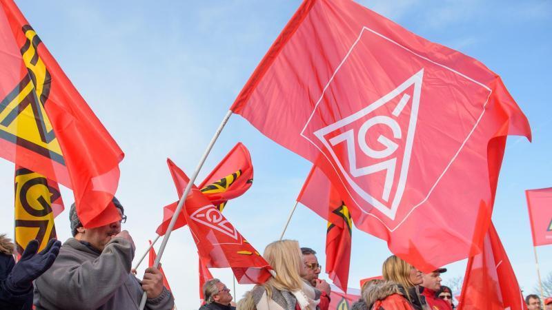 Menschen schwenken IG Metall-Flaggen. Foto: Oliver Dietze/dpa/Archivbild
