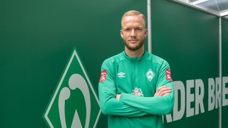 Neuzugang Kevin Vogt steht neben dem Werder-Vereinslogo bei seiner Präsentation. Foto: Kokenge/nordphoto/dpa
