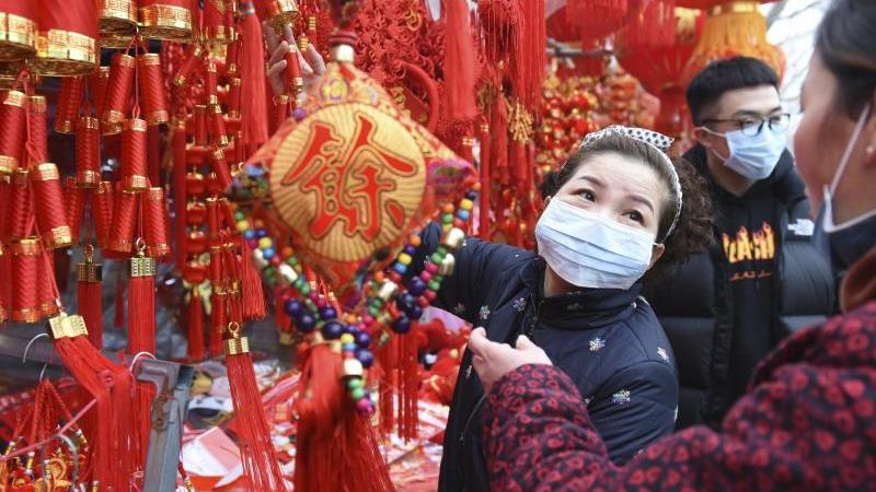 Nur mit Mundschutz: Menschen kaufen auf einem Markt in Fuyang Dekoration für das bevorstehende Neujahrsfest. Foto: CHINATOPIX/AP/dpa
