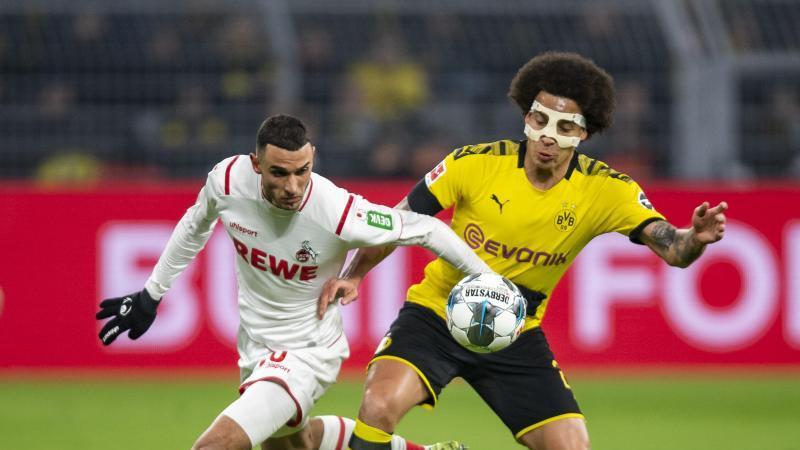 Kölns Ellyes Skhiri und Dortmunds Axel Witsel (l-r.) im Zweikampf um den Ball. Foto: David Inderlied/dpa