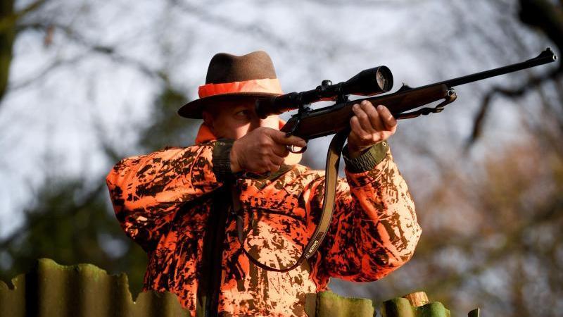 Ein Jäger steht mit dem Gewehr im Anschlag auf einem Feld. Foto: Carsten Rehder/dpa/Archivbild