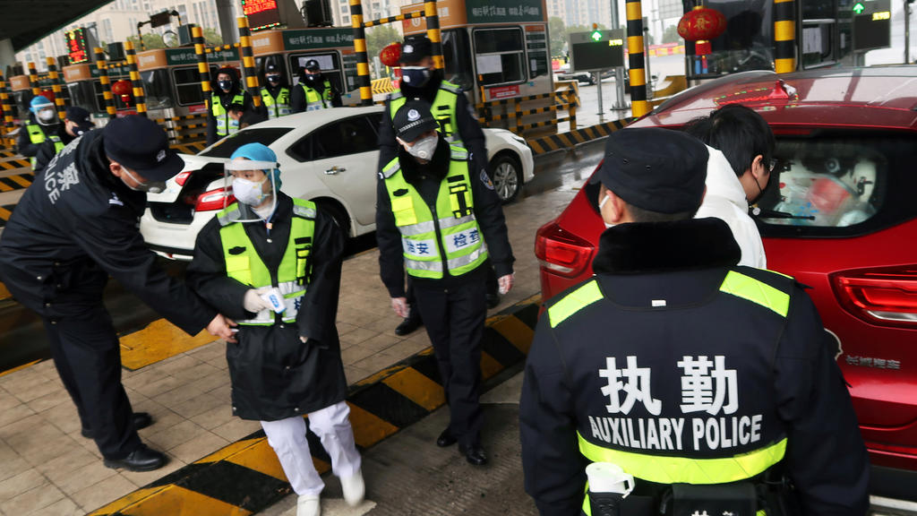 FILE PHOTO: Police officers wearing masks check the boot of a car for smuggled wild animals following the outbreak of a new coronavirus, at an expressway toll station on the eve of the Chinese Lunar New Year celebrations, in Xianning, a city borderin