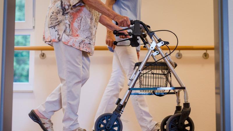 Eine Pflegekraft geht mit einer älteren Frau über einen Korridor in einem Pflegeheim. Der Mindestlohn für mehr als eine Million Pflegekräfte in Deutschland wird erhöht. Foto: Christoph Schmidt/dpa