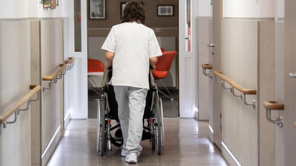 ARCHIV - 21.01.2020, Nordrhein-Westfalen, Düsseldorf: Eine Pflegerin schiebt eine Frau in ihrem Rollstuhl durch den Gang eines Altenheimes. Mehr Geld für Beschäftigte in der Altenpflege in Deutschland: Der Mindestlohn für mehr als eine Million Pflege