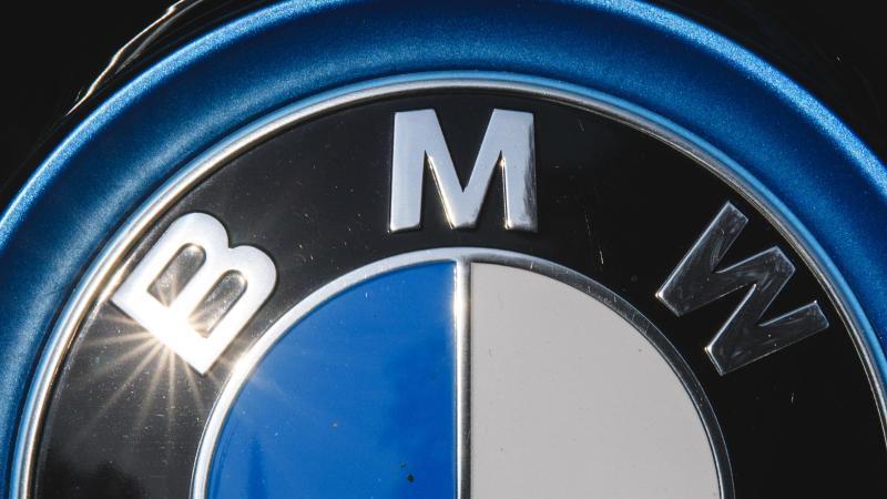 Die Sonne spiegelt sich in einem Logo des Autoherstellers BMW. Foto: Sebastian Gollnow/dpa/Archivbild