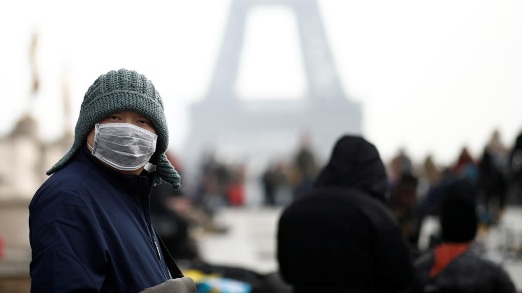 A man wears a face mask on the Trocadero esplanade in front of the Eiffel Tower in Paris, France, January 25, 2020, as France confirmed three cases of the new coronavirus. REUTERS/Benoit Tessier