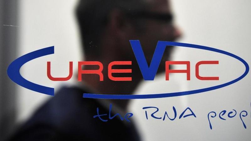 Ein Mann geht bei der Firma CureVac in Tübingen an einem Firmenlogo vorbei. Foto: picture alliance / dpa