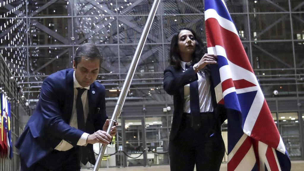 31.01.2020, Belgien, Brüssel: Mitglieder des Protokolls entfernen die Flagge des Vereinigten Königreichs aus dem Atrium des Europagebäudes. Mehr als dreieinhalb Jahre nach dem Brexit-Referendum ist Großbritannien ab dem 31.01.2020 (24 Uhr MEZ) kein M
