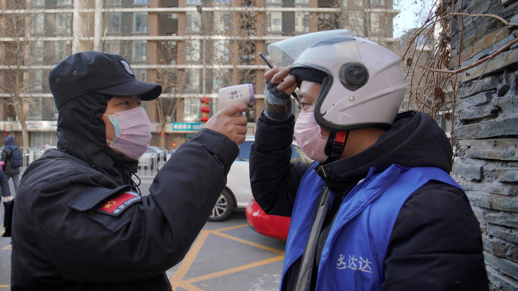 A security officer takes body temperature measurement of a delivery worker at a residential compound in Beijing, China as the country is hit by an outbreak of the new coronavirus, February 1, 2020.  REUTERS/Stringer  NO RESALES. NO ARCHIVES.