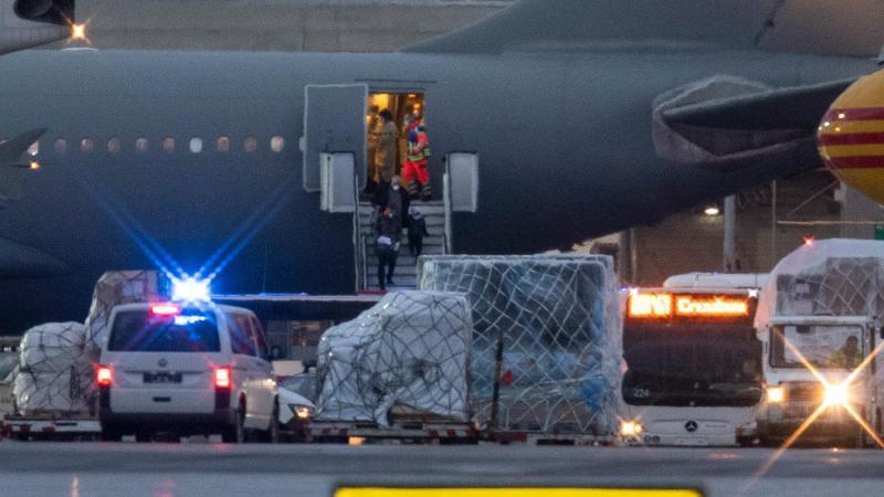 """Ein Mann und Kinder mit Mundschutzmasken verlassen den Airbus A310 """"Kurt Schumacher"""" der Luftwaffe in Richtung eines Busses, während Notärzte das Innere der Maschine betreten. Foto: Boris Roessler/dpa"""