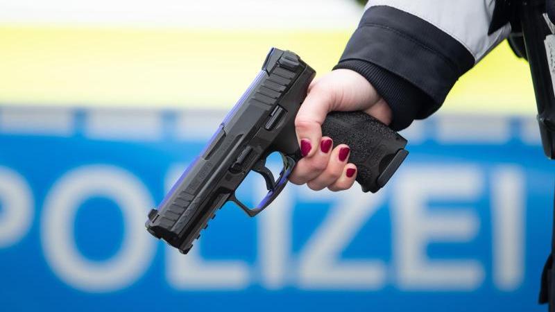 Eine Polizistin hält eine neue Dienstwaffe in der Hand. Foto: Friso Gentsch/dpa/Archivbild