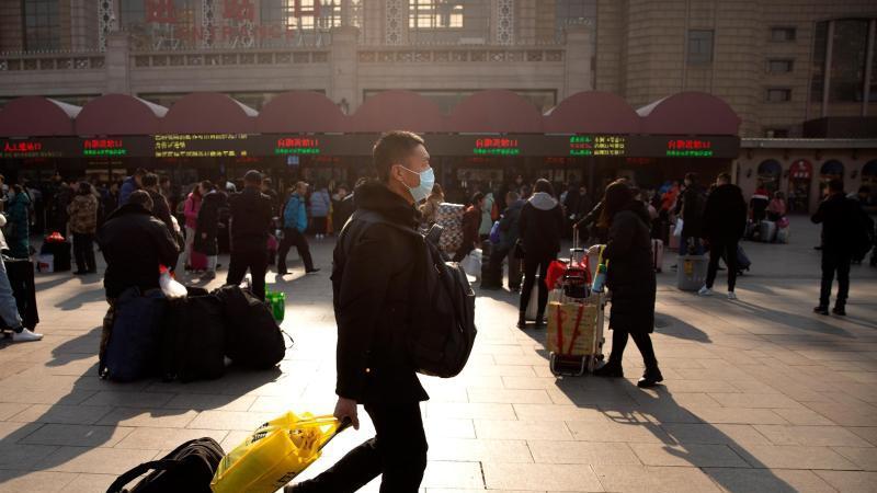 Ein Reisender trägt einen Mundschutz, während er vor dem Pekinger Bahnhof entlanggeht. Foto: Mark Schiefelbein/AP/dpa/Archiv