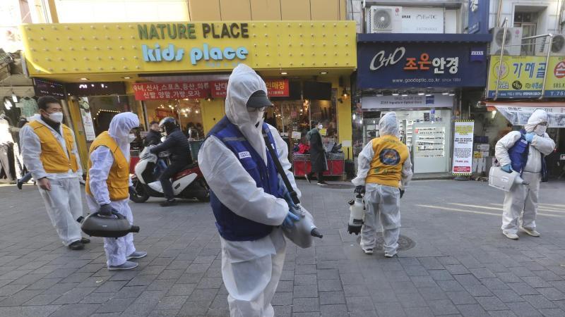 Arbeiter in Schutzkleidung versprühen auf einem Markt in Seoul Desinfektionsmittel. Foto: Ahn Young-Joon/AP/dpa