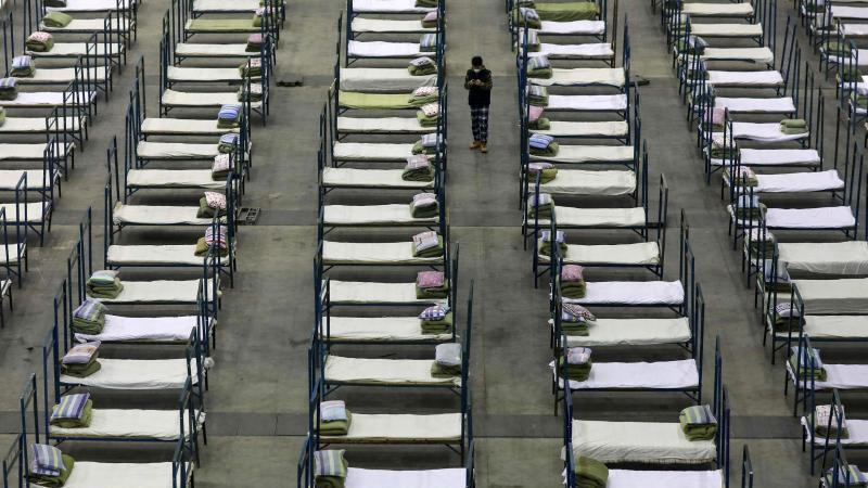 Ein Mitarbeiter steht zwischen Feldbetten, die in einem Kongresszentrum in Wuhan aufgestellt wurden. Es fehlen Betten zur Behandlung von Infizierten. Foto: -/CHINATOPIX/AP/dpa
