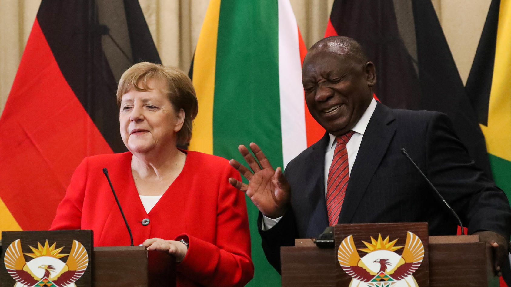 German Chancellor Angela Merkel reacts with South Africa's President Cyril Ramaphosa, during a media briefing at the Union Buildings in Pretoria