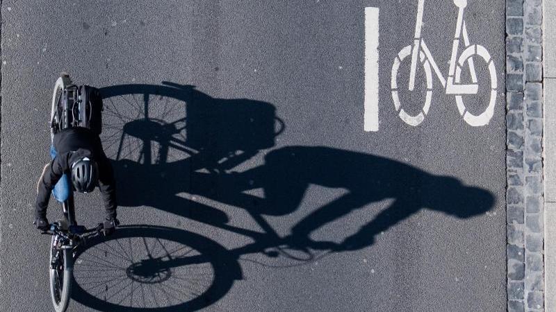 Eine Fahrradfahrerin fährt über eine Straße mit einer Markierung für Fahrräder. Foto: Julian Stratenschulte/dpa/Archivbild