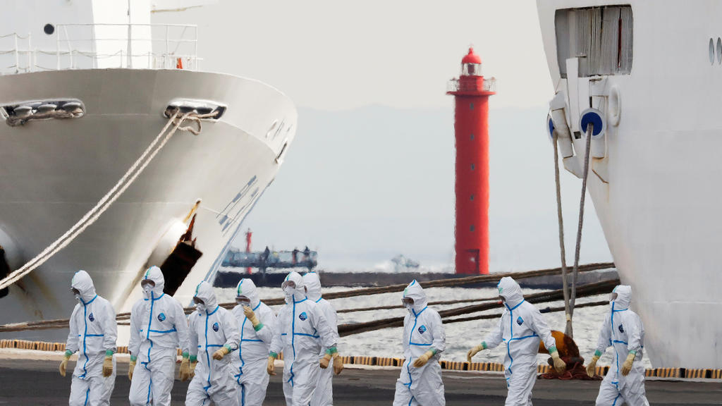 Men wearing protective gear are seen near the cruise ship Diamond Princess, where 10 more people were tested positive for coronavirus on Thursday, at Daikoku Pier Cruise Terminal in Yokohama, south of Tokyo, Japan February 7, 2020. REUTERS/Kim Kyung-