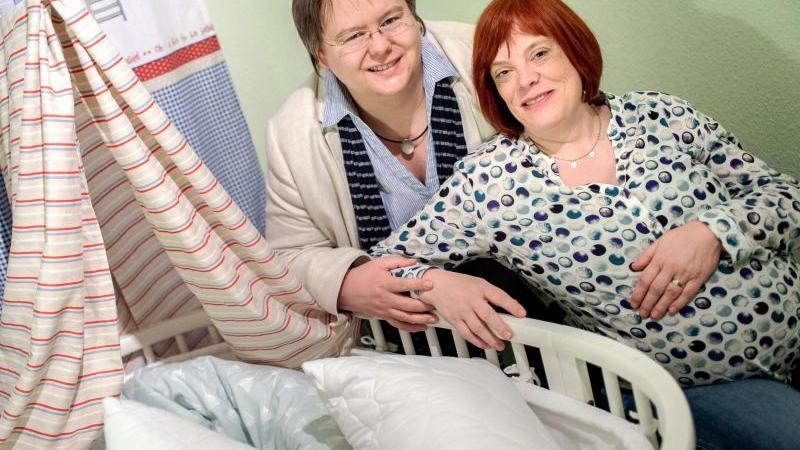 Teichert-Akkermann (r.) und ihre eingetragene Lebenspartnerin Verena Akkermann neben dem Kinderbett. Foto: Hauke-Christian Dittrich/dpa
