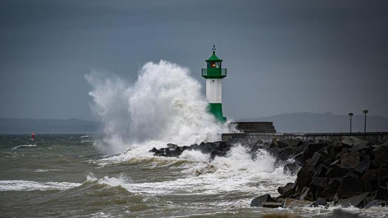 Hohe Wellen brechen an der Hafenmauer beim Leuchtturm im Sassnitzer Hafen auf Rügen. Foto: Arne Bänsch/dpa/Archivbild