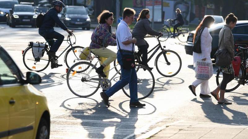Radfahrer und Fußgänger überqueren eine Straßenkreuzung. Foto: Arne Dedert/dpa/Archivbild