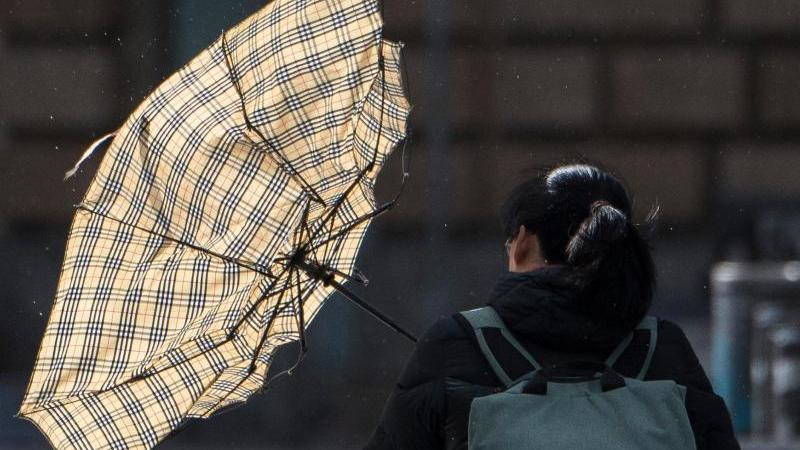 Eine heftige Sturmböe erfasst den Schirm einer Frau. Foto: Boris Roessler/dpa/Archiv
