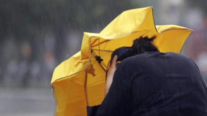 Eine Frau kämpft mit einem Regenschirm gegen Windböen. Foto: Chiang Ying-Ying/AP/dpa/Archivbild