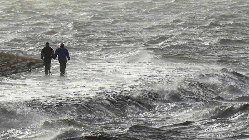 Passanten trotzen am Nordseedeich dem Sturm. Foto: Carsten Rehder/dpa