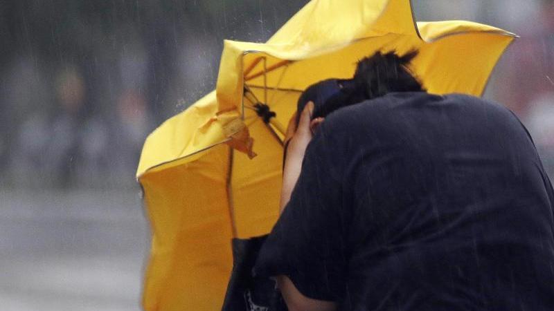 Eine Frau kämpft mir einem Regenschirm gegen Windböen. Foto: Chiang Ying-Ying/AP/dpa/Archivbild