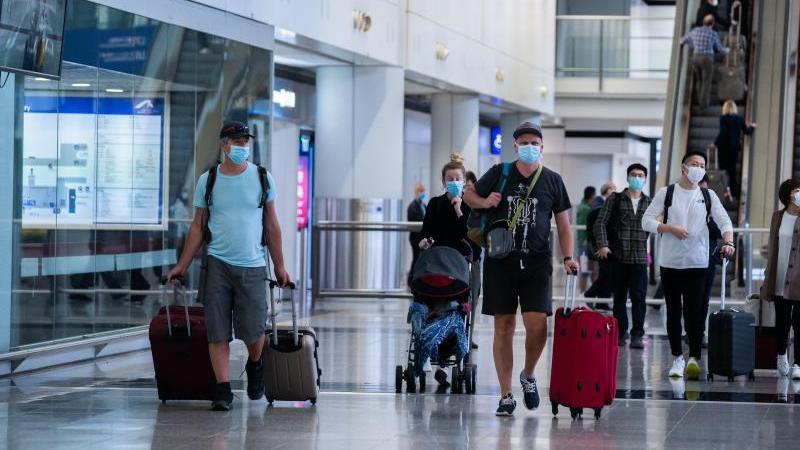Reisende mit Mundschutz am Flughafen Hong Kong. Foto: Geovien So/SOPA Images via ZUMA Wire/dpa/Archivbild