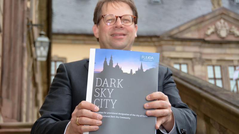Oberbürgermeister Heiko Wingenfeld (CDU) präsentiert die Bewerbung zur Dark-Sky-Community vor dem Fuldaer Stadtschloss. Foto: Jörn Perske/dpa/Archiv