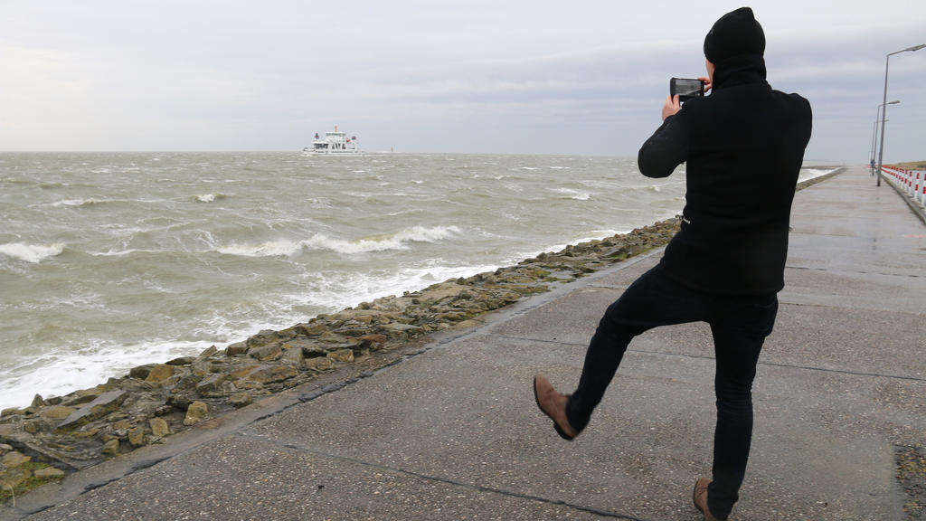 """09.02.2020, Niedersachsen, Norderney: Ein Mann macht auf der Strandpromenade auf der Nordseeinsel Norderney ein Foto von der vorbeifahrenden Autofähre. Die ersten Ausläufer des Sturmtiefs """"Sabine"""" haben die Nordsee erreicht. Foto: Volker Bartels/dpa"""